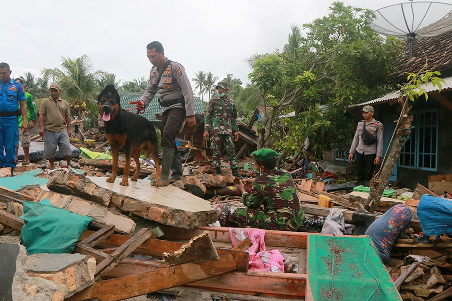 Rescue workers use a dog to search victims among debris after a tsunami hit Sunda Strait at Rajabasa in South Lampung, Indonesia on December 25, 2018 — Reuters photo