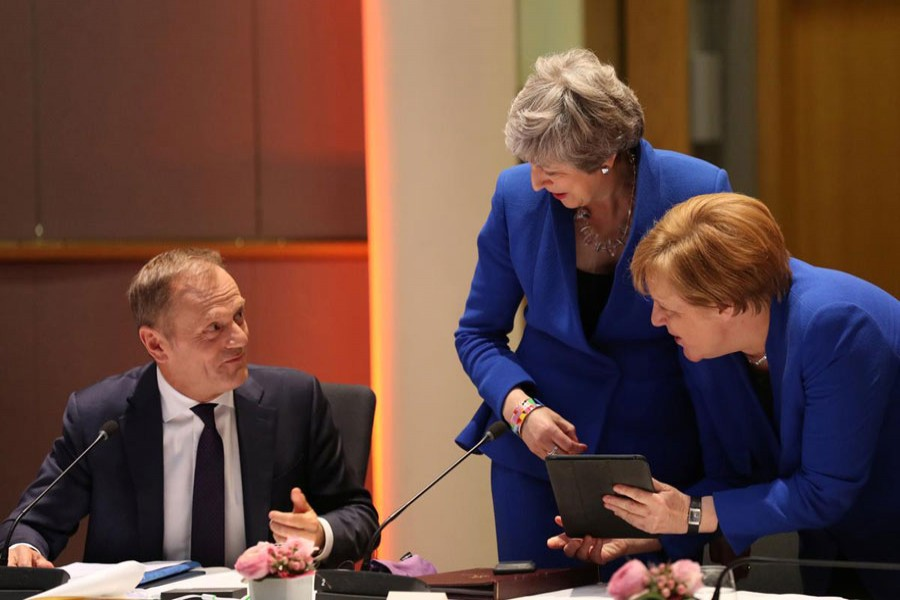 Britain's Prime Minister Theresa May and Germany's Chancellor Angela Merkel look at a tablet next to European Council President Donald Tusk, ahead of a European Council meeting on Brexit at the Europa Building at the European Parliament in Brussels, Belgium April 10, 2019. Kenzo Tribouillard/Pool via Reuters