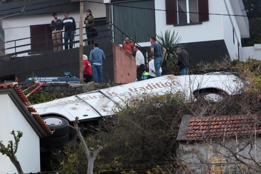 People stand next to the wreckage of a bus after an accident in Canico, in the Portuguese Island of Madeira, April 17, 2019 - REUTERS/Duarte Sa