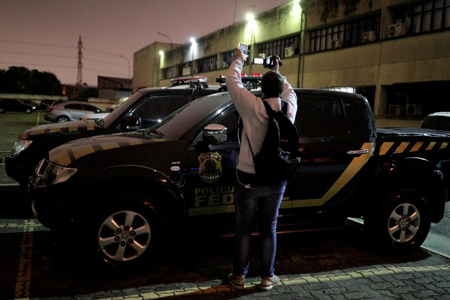 A cameraman records pickup trucks with livery resembling Brazil's federal police inside the DEIC (State Criminal Investigation Department), which were used by thieves during the theft at Guarulhos airport in Sao Paulo, Brazil on July 25, 2019 — Reuters photo