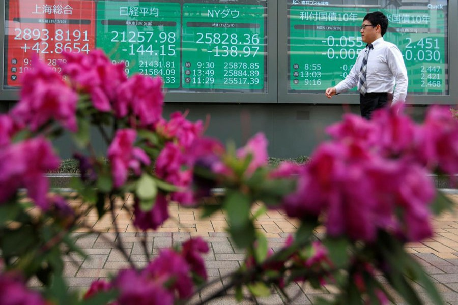 A passerby walks past in front of a stock quotation board outside a brokerage in Tokyo, Japan, May 10, 2019. Reuters/Files