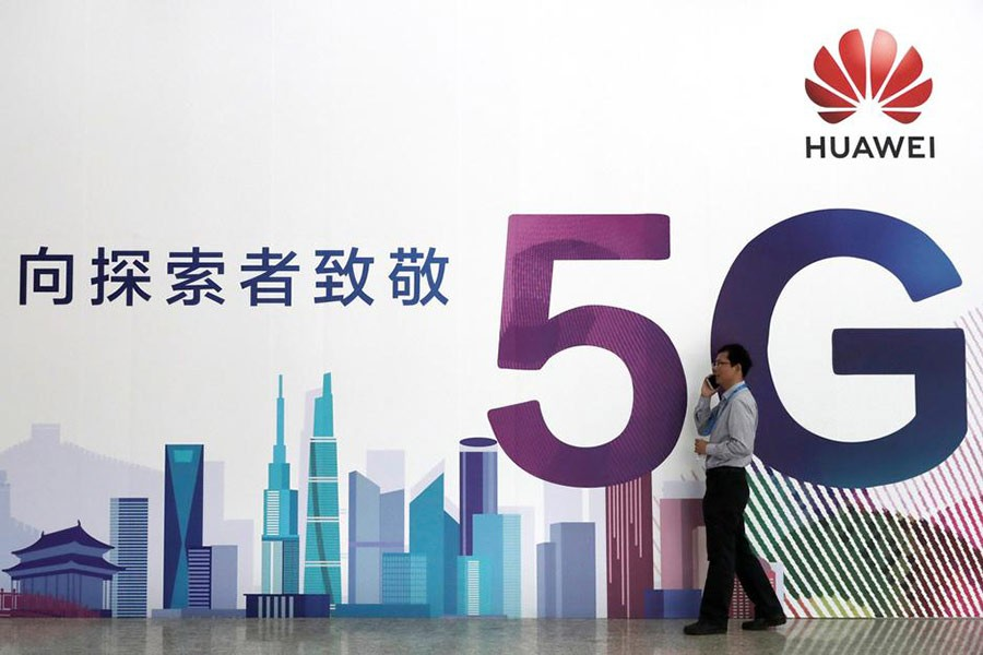 A man talks on his phone beside a Huawei billboard featuring 5G technology.  —Photo: Reuters