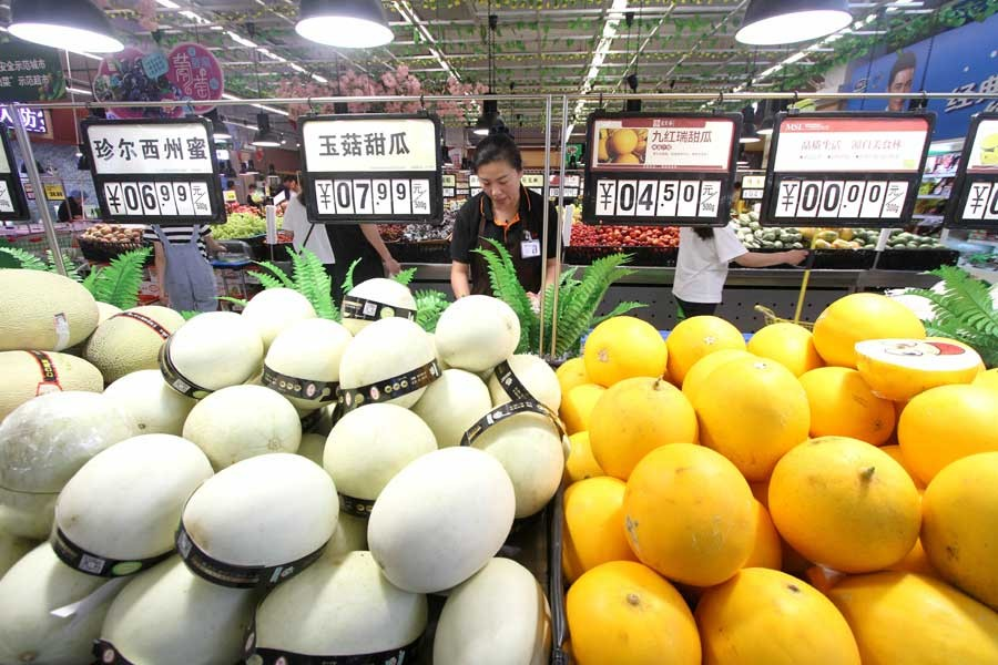 A saleswoman arranges fruit at a supermarket in Handan, north China's Hebei Province, June 12, 2019. - Xinhua