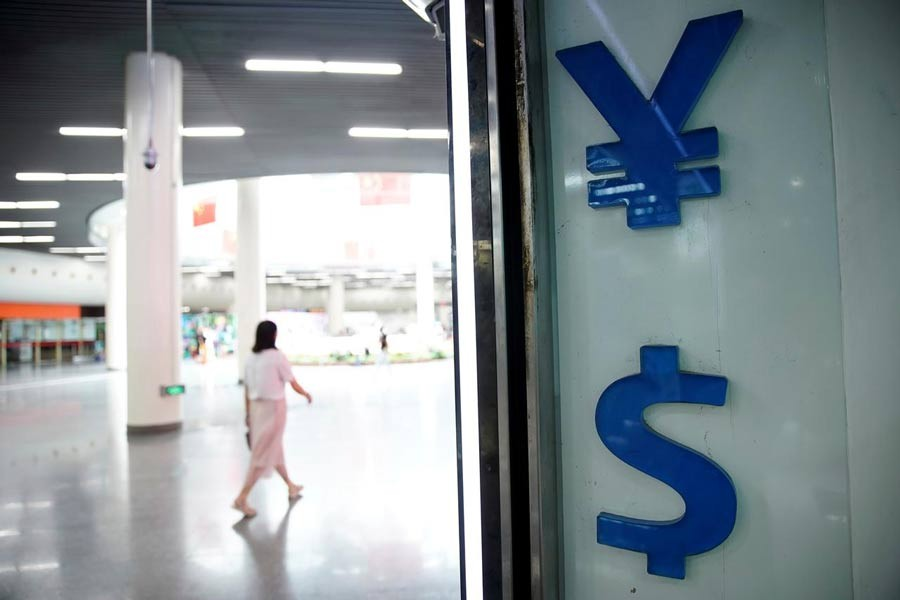 Signs of Chinese yuan and US dollar are seen at a currency exchange store in Shanghai, China — Reuters