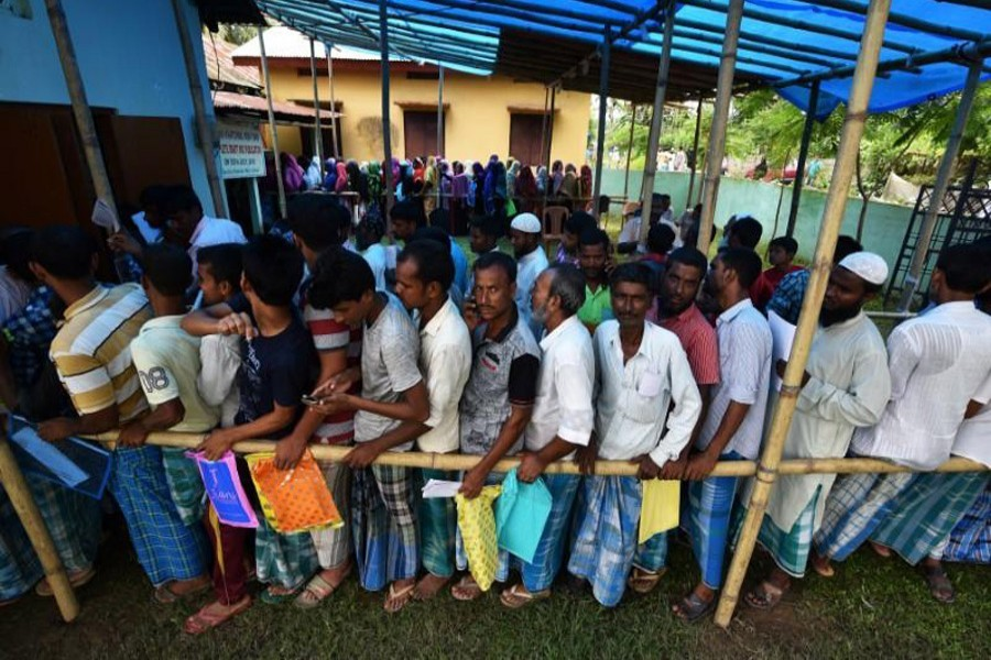 People wait in queue to check their names on the draft list at the National Register of Citizens (NRC) centre at a village in Nagaon district, Assam state, India, July 30, 2018. Reuters