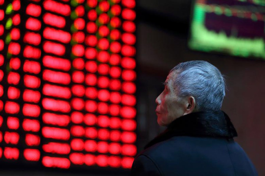 A man looks on in front of an electronic board showing stock information at a brokerage house in Nanjing, Jiangsu province, China, February 13, 2019. Reuters/File photo