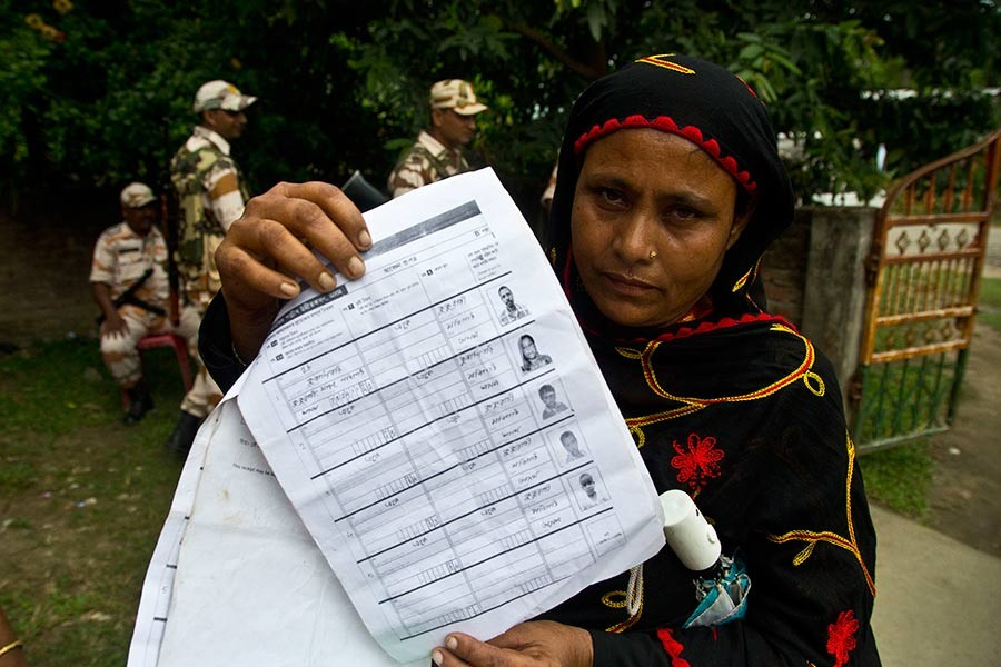 A woman displaying a document that shows inclusion of her name in the final list of the National Register of Citizens (NRC) in the Indian state of Assam on August 31, 2019. —AP Photo