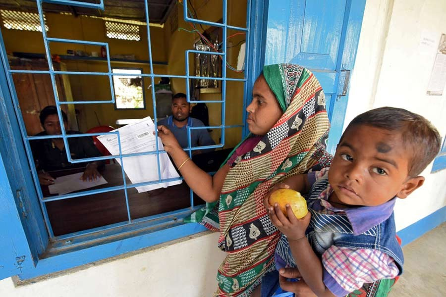 The file photo shows a woman, along with her son, trying to check her name on the draft list of the National Register of Citizens (NRC) at an NRC centre in the northeastern state of Assam, India. -Reuters Photo