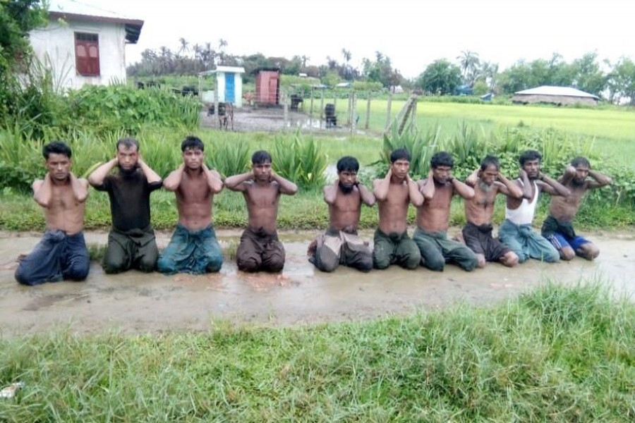 Ten Rohingya Muslim men with their hands bound kneel in Inn Din village on September 1, 2017. They are said to have been executed by Myanmar soldiers and dumped in a shallow grave. Handout via Reuters