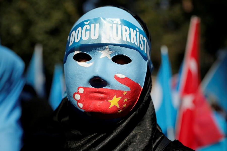 FILE PHOTO: An ethnic Uighur demonstrator wears a mask as she attends a protest against China in front of the Chinese Consulate in Istanbul, Turkey, October 1, 2019. REUTERS/Huseyin Aldemir