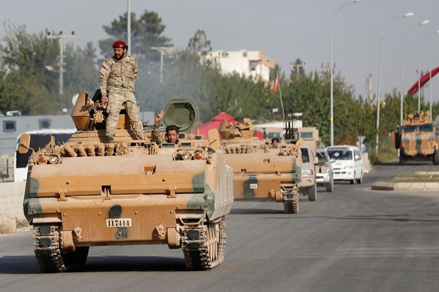 Members of Syrian National Army, known as Free Syrian Army, drive in an armoured vehicle in the Turkish border town of Ceylanpinar in Sanliurfa province, Turkey on October 11, 2019 — Reuters photo