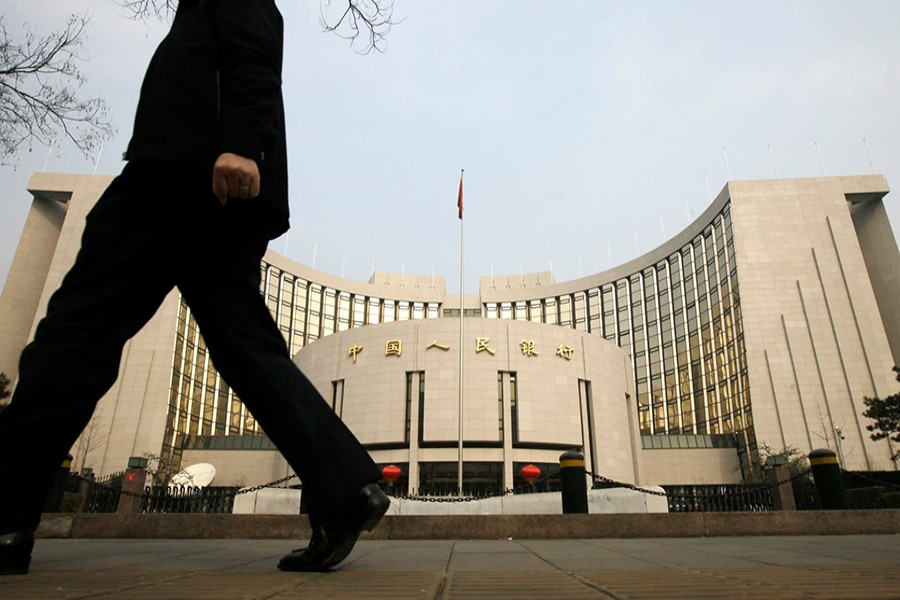 A man walks past the headquarters of the People's Bank of China (PBOC), the central bank, in Beijing — Reuters/Files