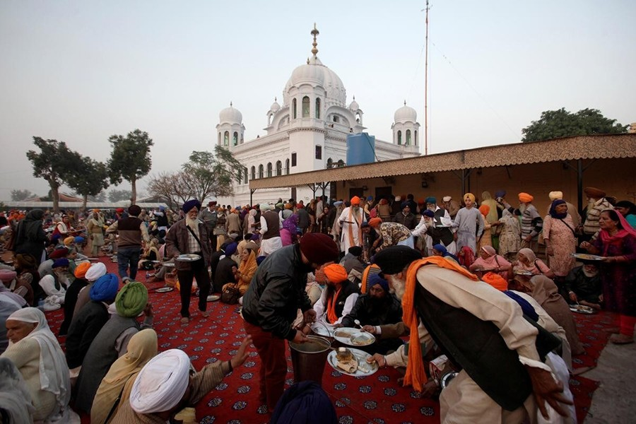 A man serves food to Sikhs from India outside the shrine of Guru Nanak Dev Ji, founder of Sikhism, during the groundbreaking ceremony of the Kartarpur border corridor, which will officially open November next, in Kartarpur, Pakistan on November 28, 2018 — Reuters/Files
