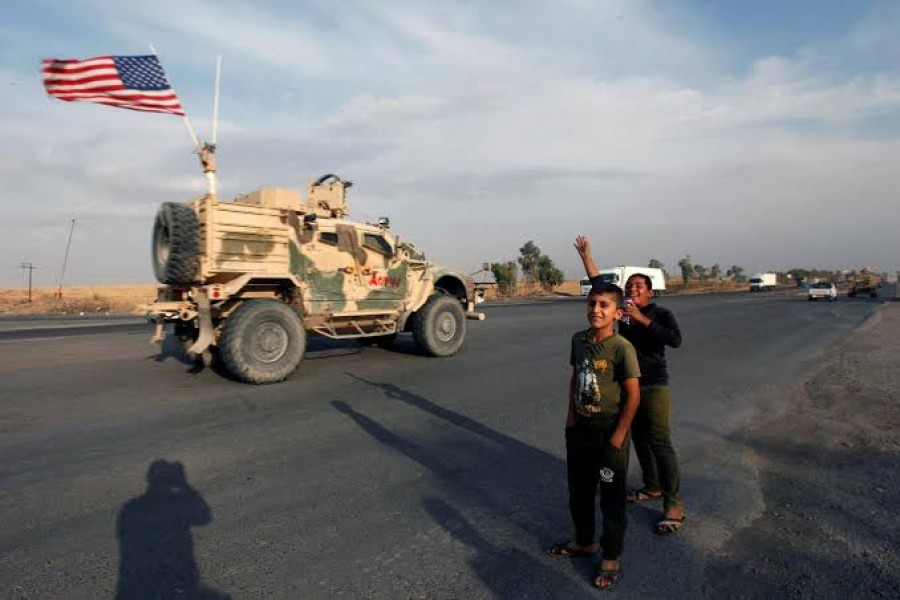 Boys wave towards a convoy of U.S. vehicles withdrawing from northern Syria, in Erbil, Iraq October 21, 2019. REUTERS/Azad Lashkari