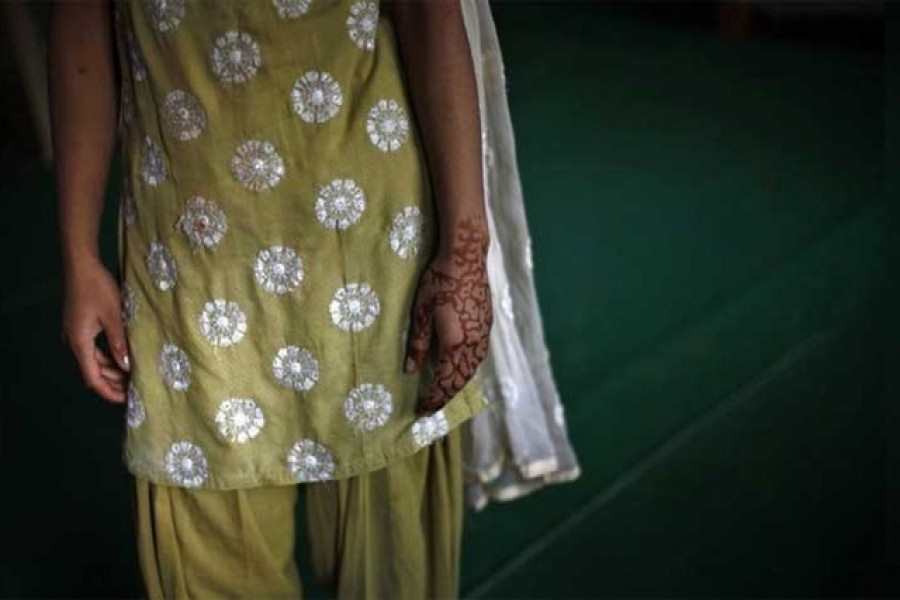 A 16-year-old girl with her hand decorated with henna stands inside a protection home on the outskirts of New Delhi, November 9, 2012. Reuters/Files