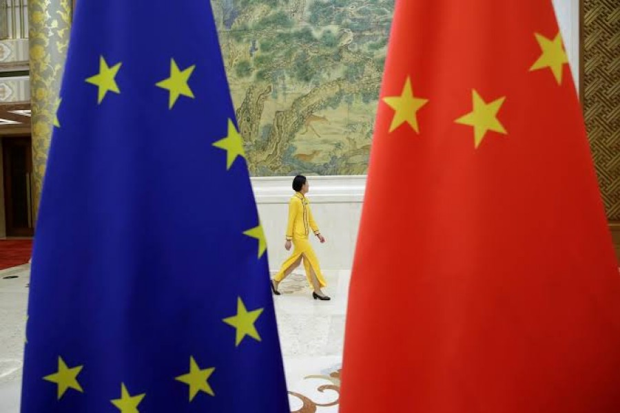 FILE PHOTO: An attendant walks past EU and China flags in Beijing, China June 25, 2018. REUTERS/Jason Lee