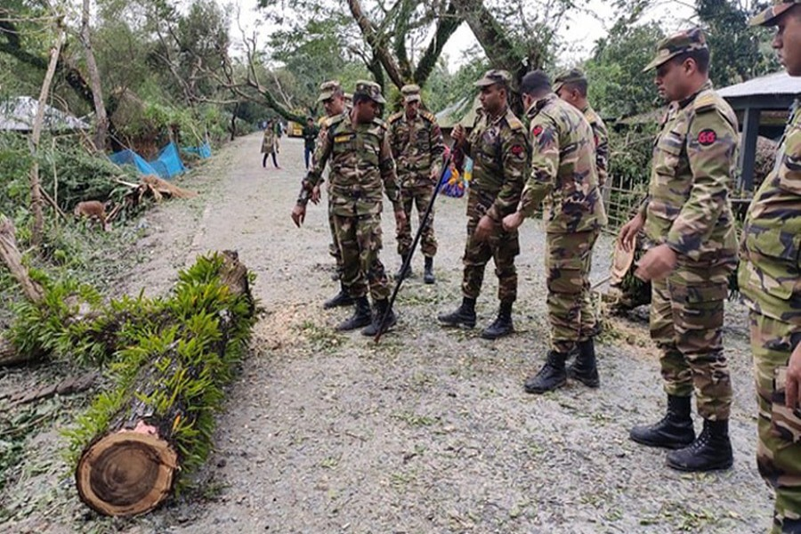 Members of Bangladesh Army removing an uprooted tree from a road in Satkhira as cyclone 'Bulbul' lashes coastal districts early Sunday