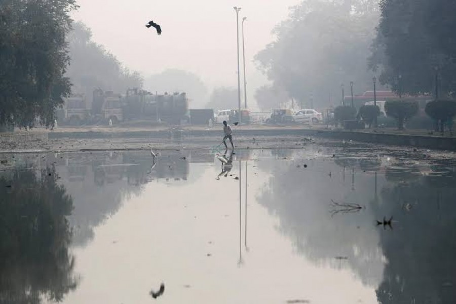 A man cleans a pond on a smoggy morning in New Delhi, November 11, 2019. REUTERS/Adnan Abidi