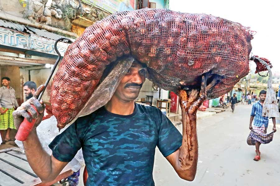 A labourer carrying a sack of rotten onion purchased by a retailer from Shyambazar wholesale market in the city on Friday at a price of Tk 105 per kg — FE photo