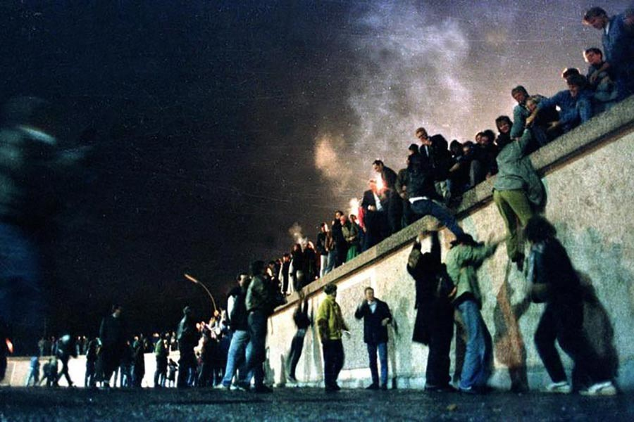East German citizens climbing the Berlin wall at the Brandeburg gate after the opening of the East German border was announced, November 10, 1989. -Reuters file photo