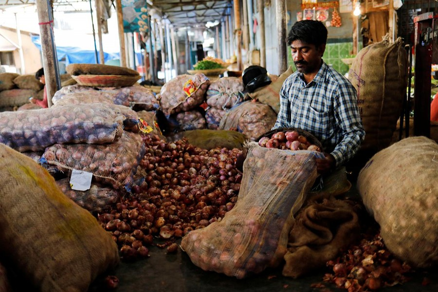 A vendor puts onions in a sack after sorting them at a vegetable market in Mumbai on June 12, 2018 — Reuters/Files