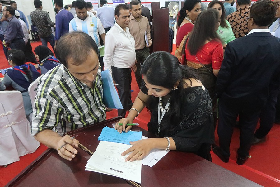 A tax official helping a man file his tax return at the Tax Fair at the Officers Club in the city on its concluding day on Wednesday — FE photo