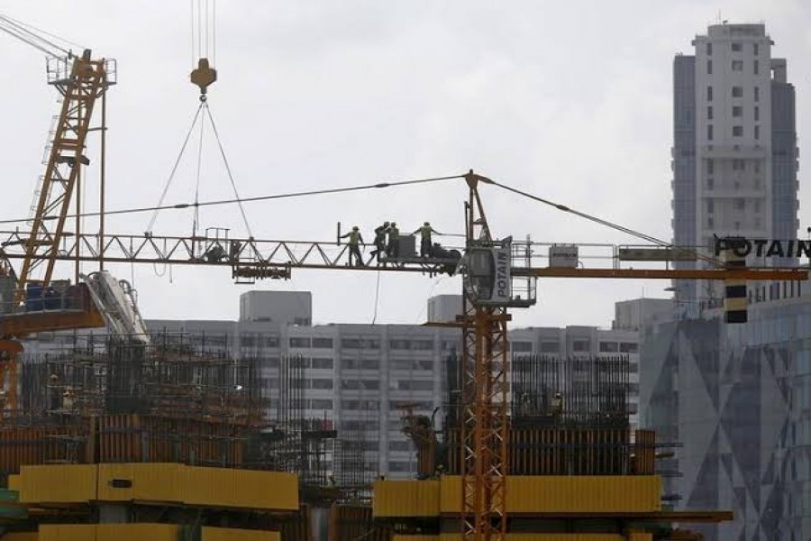 Workers stand on a crane at the construction site of a residential complex in Mumbai, India, May 27, 2015. REUTERS/Shailesh Andrade