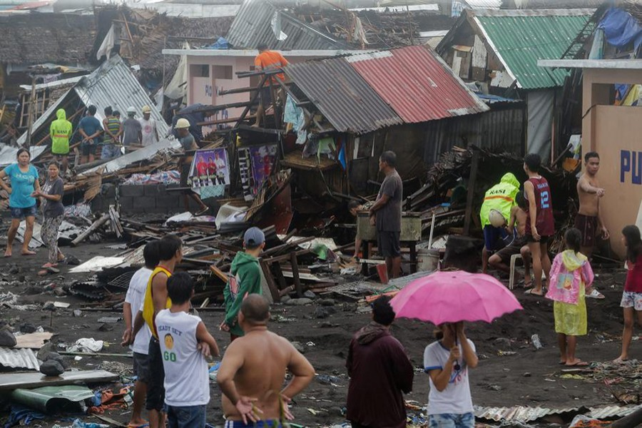 Residents stand among their damaged houses after Typhoon Kammuri hit Legazpi City, Albay, Philippines on Monday — Reuters photo