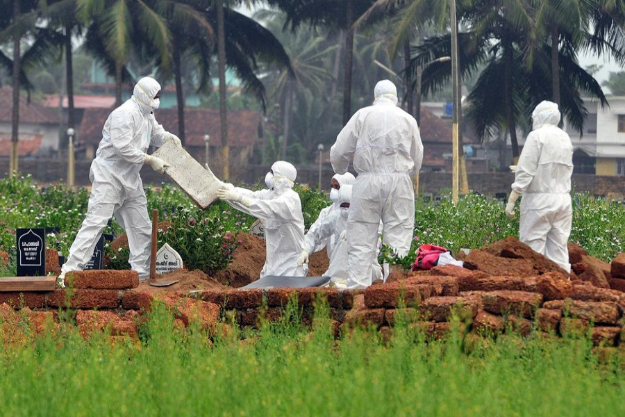 Doctors and relatives wearing protective gear dig a grave to bury the body of a victim, who lost his battle against the brain-damaging Nipah virus, during his funeral at a burial ground in Kozhikode, in the southern Indian state of Kerala, May 24, 2018. Reuters/File Photo