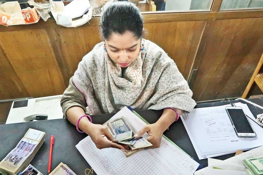 A bank staffer checking notes at a counter of her commercial bank in Dhaka — FE photo