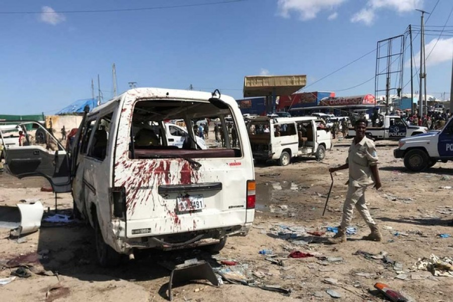 Somali security assess the scene of a car bomb explosion at a checkpoint in Mogadishu, Somalia, December 28, 2019. Reuters