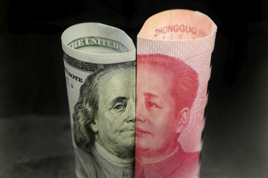 A Benjamin Franklin US 100 dollar banknote and a Chinese 100 yuan banknote with late Chinese Chairman Mao Zedong are seen in this picture illustration in Beijing, China, January 21, 2016. Reuters/File Photo