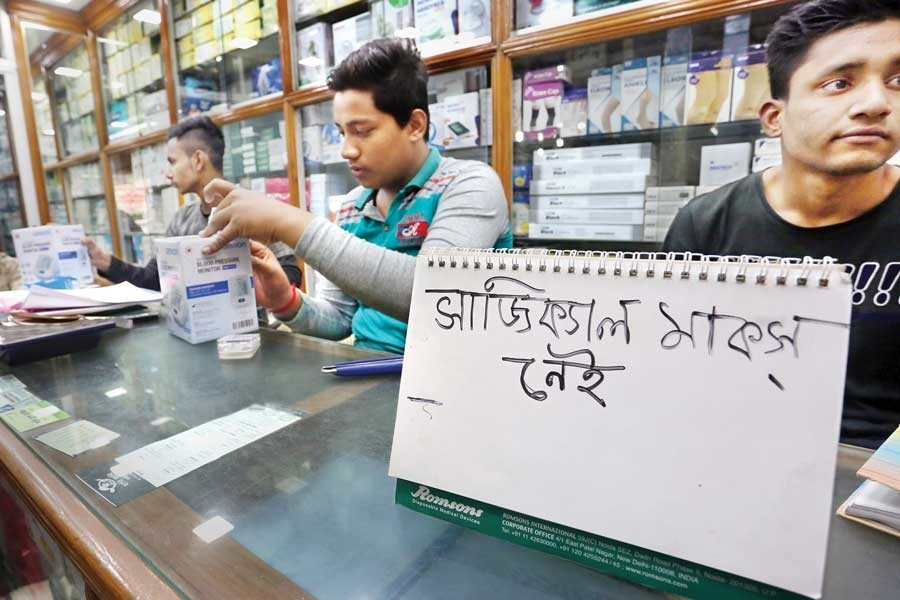 A shop at Topkhana Road in the city displays the 'No surgical masks available' sign on Thursday following scarcity of the item in the wake of coronavirus outbreak in China — FE photo