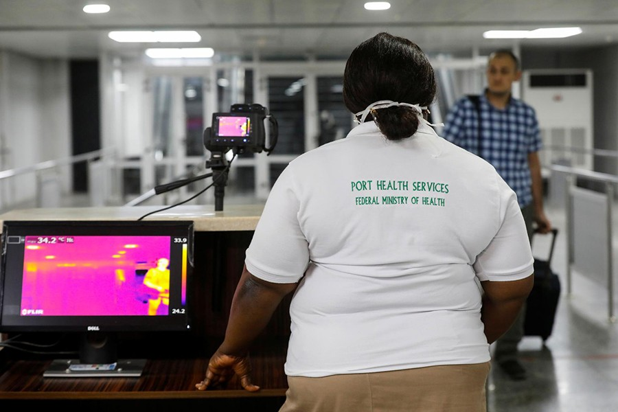An official monitors thermal scanners as a passenger walks past upon arrival of a flight into Lagos, Nigeria on January 22, 2020 — Reuters/Files