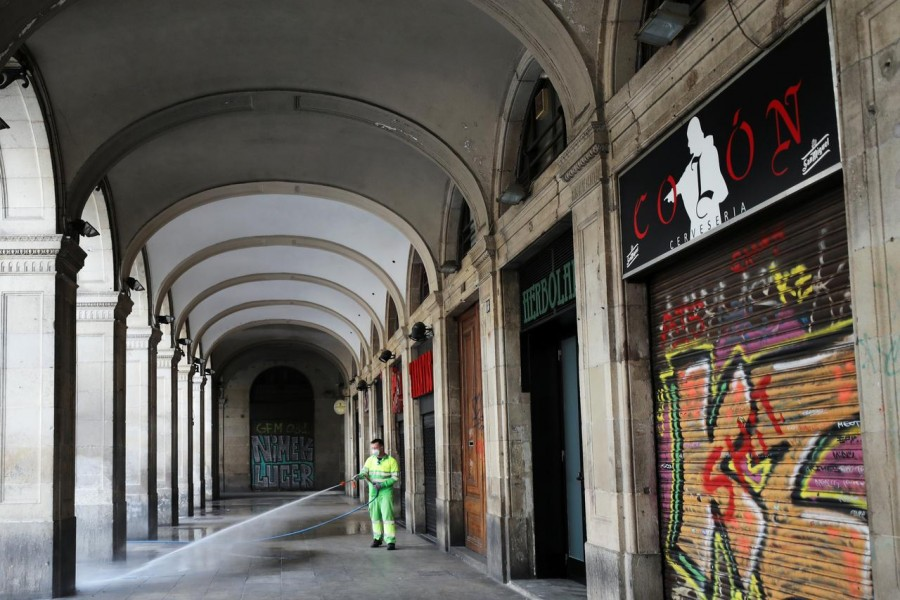A worker wears a protective face mask as he washes the empty Plaza Reial (Reial Square), amidst concerns over coronavirus outbreak, in Barcelona, Spain March 14, 2020. REUTERS/Nacho Doce