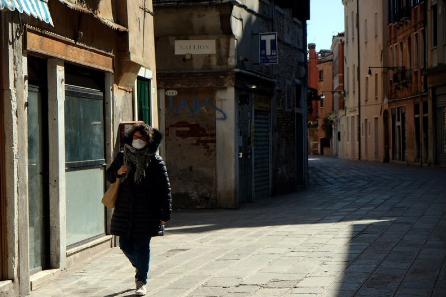 A woman wearing a protective mask in an empty street of Venice on Sunday with an unprecedented lockdown across of all Italy imposed to slow the outbreak of coronavirus, in Venice, Italy on March 15. 2020 — Reuters photo