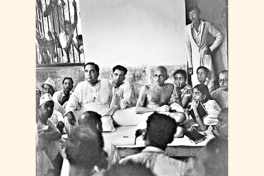 Sheikh Mujibur Rahman, the young student leader (standing at the back) and Huseyn Shaheed Suhrawardy with Mahatma Gandhi in Kolkata. They were there to support Mahatma Gandhi's protest against the Hindu-Muslim communal riots (1947) — mujib100.gov.bd