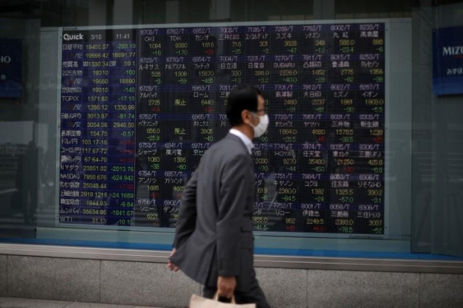 A man wearing protective face mask, following an outbreak of the coronavirus disease (COVID-19), walks in front of a stock quotation board outside a brokerage in Tokyo, Japan, March 10, 2020. — Reuters