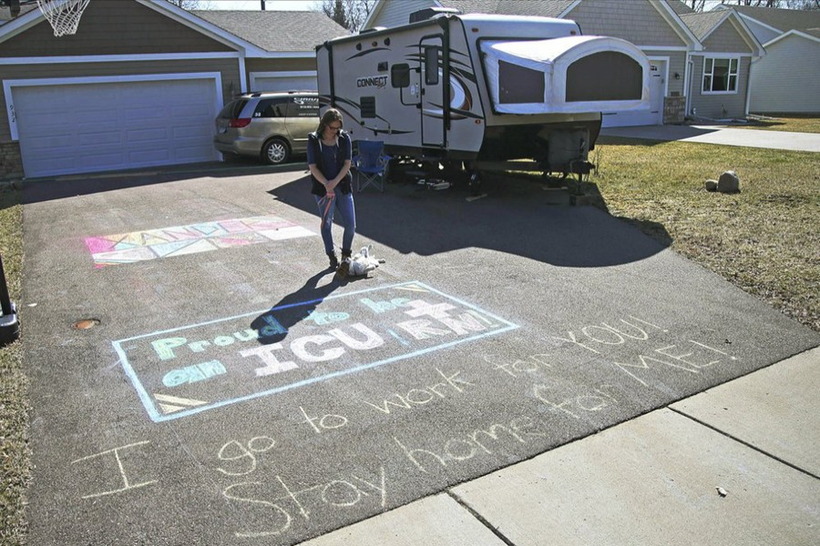 In this April 1, 2020, photo, Lisa Neuburger stands with her dog Bella by the camper she is living in and the chalk message she made in her former in-laws' driveway in St Paul Park, Minn Neuburger is living in the camper after being exposed to the coronavirus as an ICU nurse — AP photo