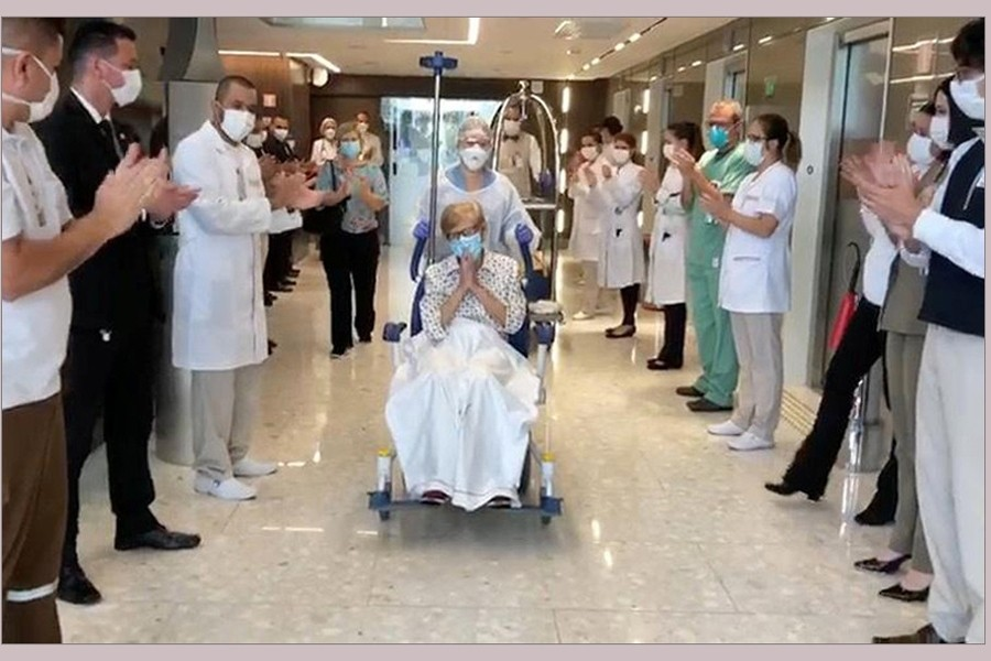 97-year-old Brazilian Gina Dal Colleto, the oldest known survivor of the coronavirus disease (COVID-19) in Brazil, is pushed in a wheelchair out of Sao Paulo's Vila Nova Star hospital to applause from doctors and nurses on April 12, 2020, in this still image obtained from a social media video — Courtesy of Rede D'Or Sao Luiz/Social Media via REUTERS