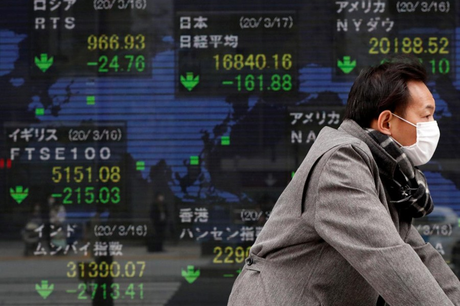 A man wearing a protective face mask following an outbreak of the coronavirus disease (COVID-19) walks past a screen displaying the world's markets indices outside a brokerage in Tokyo, Japan on March 17, 2020 — Reuters/Files