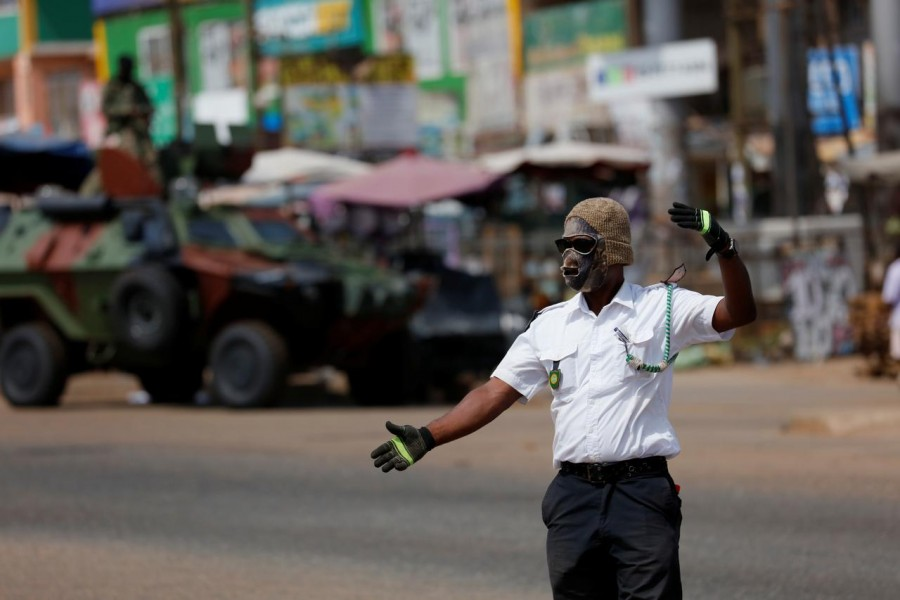 FILE PHOTO: A security personnel from town council wears a face mask while he controls traffic, as Ghana enforces partial lockdown in the cities of Accra and Kumasi to slow the spread of the coronavirus disease (COVID-19) in Madina neighborhood of Accra, Ghana, March 31, 2020. REUTERS/Francis Kokoroko