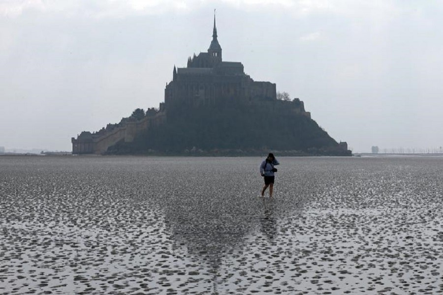 Representational image: A woman walks on the sand at low tide around the Mont Saint-Michel 11th century abbey off France's Normandy coast March 21, 2015. — Reuters/Files