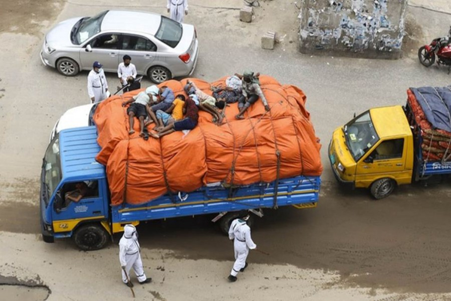 Travellers lie on a goods-laden truck to hide from the police at a check-post set up in Dhaka's Uttara to control the movement of people in and out of the city as part of efforts to slow the spread of coronavirus. Photo: bdnews24.com