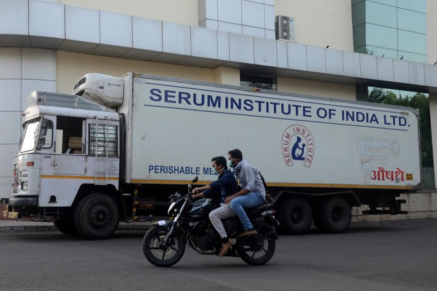 Men ride on a motorbike past a supply truck of India's Serum Institute, the world's largest maker of vaccines, which is working on a vaccine against the coronavirus disease (COVID-19) in Pune, India, May 18, 2020. — Reuters