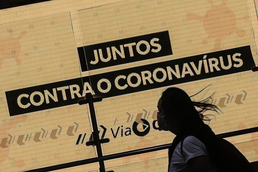 """A woman passes by a placard reading """"Together against coronavirus"""" in Sao Paulo, Brazil, on May 20, 2020. (Xinhua/Rahel Patrasso)"""