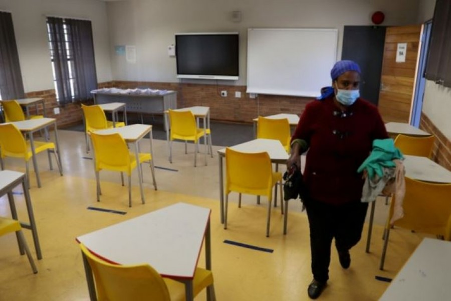 A worker walks past safely spaced desks following safe distancing measures amid the COVID-19 outbreak, at the Seshegong secondary school in Olivenhoutbosch, South Africa, May 28, 2020. /Reuters