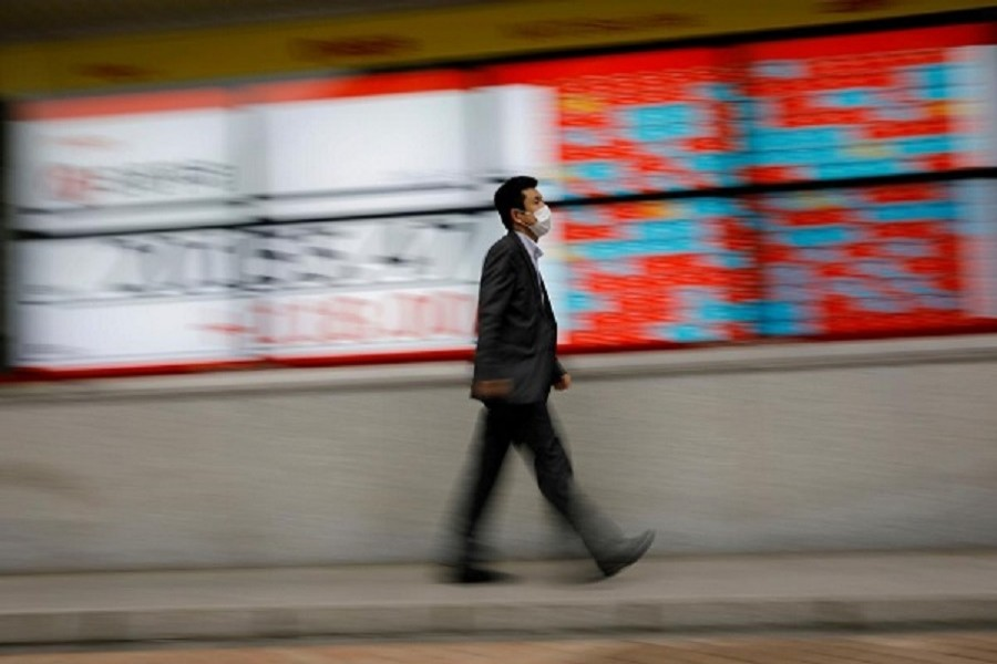 A man wearing a protective face mask, following the coronavirus disease (Covid-19) outbreak, walks in front of a stock quotation board outside a brokerage in Tokyo, Japan, May 18, 2020 — Reuters/Files