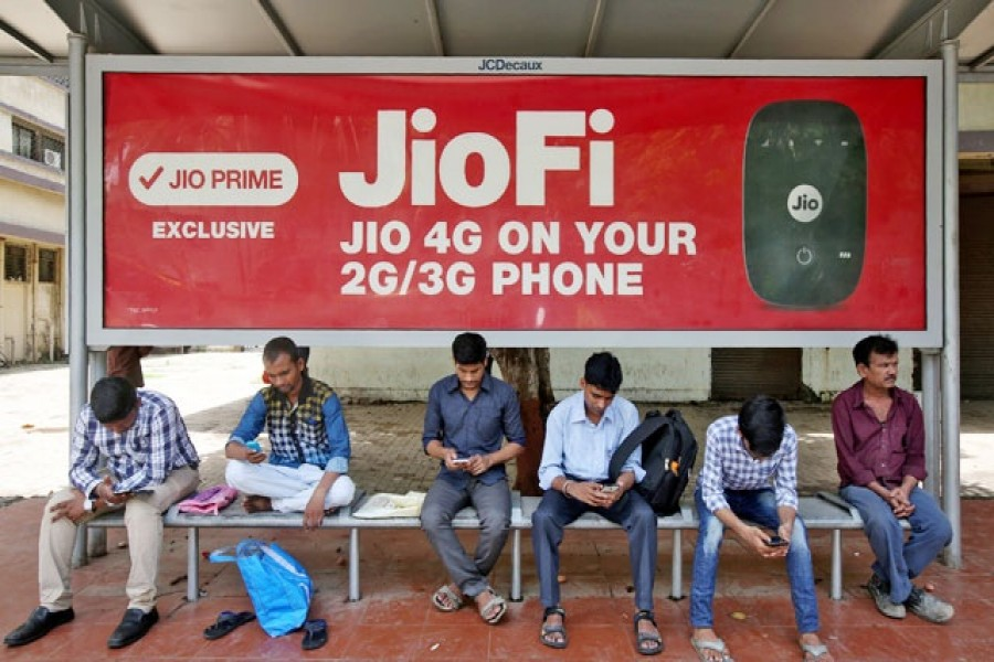 Commuters use their mobile phones as they wait at a bus stop with an advertisement of Reliance Industries' Jio telecoms unit, in Mumbai, India Jul 10, 2017. REUTERS