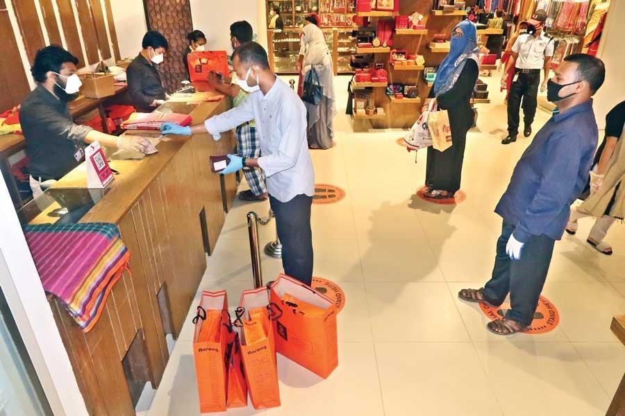 Customers maintain social distancing while doing shopping at an Aarong outlet at Wari in Dhaka city, May 10, 2020 — FE Photo/Files